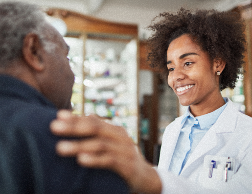Female pharmacist smiling and putting hand on customer's shoulder.